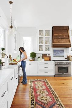A salvaged wood hood, custom-built by Tim, and a Turkish runner add warmth to the mostly white kitchen.