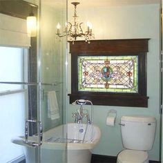 Vintage details normally reserved for other rooms also work well in the water closet. A stained glass window, chandelier, and soaker make for a relaxing period corner in a modern bath.