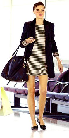 Miranda Kerr looks darling Down Under in a striped tunic topped with a long blazer, bow-topped flats and matching satchel at Brisbane Airport