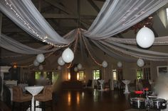 Ceiling 'canopy' with 2 layers of white wedding tulle, white Christmas lights that have white wire, 2 foot round balloons hung over beams in ballroom.