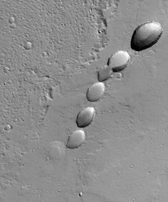 Chain of Collapse Pits Near Ascraeus Mons - This Mars Global Surveyor (MGS) Mars Orbiter Camera (MOC) image shows a chain of collapse pits on a dust-mantled, lava-covered plain northeast of Ascraeus Mons—one of the giant volcanoes located in the Tharsis region of Mars. Pit chains are associated with collapse which may be driven by several processes including crustal extension owing to tectonic processes and the collapse of the roof of a lava tube. Credit: NASA/JPL/Malin Space Science Systems