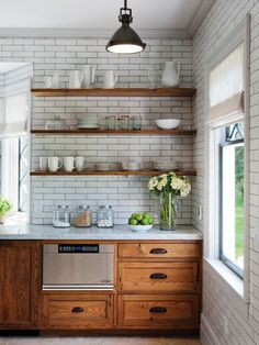 Chunky wood shelves break up a floor-to-ceiling wall of classic subway tiles.