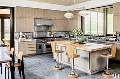Aero Studios created the oak cabinetry in the kitchen; the billiard light is a Thomas O'Brien design from Aero, the range and hood are by Wolf, and the barstools are by Soane Britain   Grey, white, light wood, stainless steel.