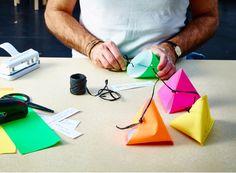 Fes formes de piràmides amb folis de colors, grapa-les, fica-hi unes notes amb missatges i lliga-ho tot. Col·loca-les als plats dels convidats perquè cadascú tingui el seu regalet.