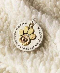 "Share the love for your furry companion with this endearing accessory. Our sterling silver disk pendant is decorated with a raised paw print and etched heart accenting the sentiment: ""A mother understands what her pet doesn't say."" The necklace is made complete with a delicate purple crystal in the center. Every purchase helps animals in need!"