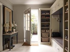Taupe mudroom features a taupe built-in bench accented with a black shiplap backsplash with overhead cabinets flanked by taupe built-in shoe shelves.