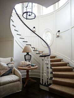 This wide front hall has plenty of room for a winding staircase. The stair runner softens the look of the wooden risers, while a dark wood railing draws the eye up and around the shapely curve of the staircase. Winding Staircase, Staircase Railings, Curved Staircase, Modern Staircase, Wood Railing, Stairways, Spiral Staircases, Bannister, White Staircase