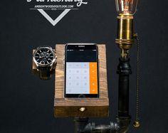 Ici, nous avons intégrer notre éclairage industriel signature avec téléphone & watch station d'accueil. Servir comme un morceau parfait pour votre bureau ou de chevet luminosité ambiante. Poncé grossièrement plaque de bois et solide cadre en tube métal donne un accent industriels fort et douille en laiton de haute qualité ramène beaucoup de détails.  Modèle de téléphone affichage est trou iPhone 6, pré-percées pour câble de charge Trou de Apple montre pour le chargeur. Le trou fait pour elle…