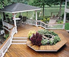 Ground level deck with covered area. Stairs & landings from upstairs windowed porch. Benches around hot tub converted to pond/planter. Designed and built by Atlanta Decking.