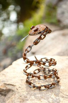 Metal Sculpture Snake Here's another sculpture I welded! This guy is made from a chain, two spoons and a lobster pick. It was tricky to get him to be free-standing, so we nailed the chain around a log...