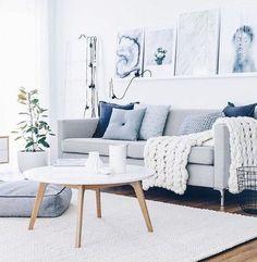 salon zen, canapé gris sur un fond essentiellement en blanc, jolis tableaux d'art moderne, coussins bleus qui apportent de la couleur