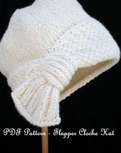 "You can knit this haute cloche hat yourself. The main attraction is the crisscross stitch pattern band ending with a decorative ""fan"" to capture your eye. You can wear the fan near your ears or down lower by your neck, near your nape.  Please Note: This listing is for a PDF Pattern and not the actual hat. If you wish to purchase the actual hat, please go to the hat section in my flagship shop. http://www.etsy.com/shop/ohmay?section_id=7152326  Skill Level: Challenging..."