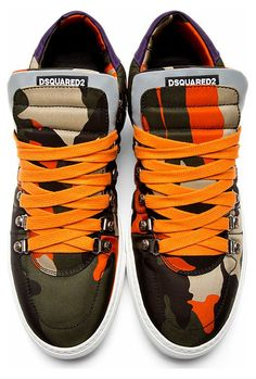 Green & Orange Camo Low-Top Sneakers by Dsquared2. Textile sneakers in tones of green and orange. Camouflage pattern throughout. Round toe. Orange lace-up closure with d-rings and lace hooks at front collar. Padded oversize bellows tongue. Padded collar. Accent paneling at heel in purple. White rubber sole.  http://www.zocko.com/z/JFKVp
