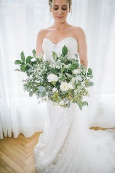 This bride carried a beautiful white rose and greenery filled bouquet for her big day | Image by Anna + Mateo