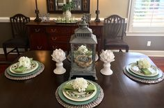 Spring dinning room table scape! Hydrangea napkin holders, artichoke candle holders, classic lantern with a bird a nest inside versus a candle.