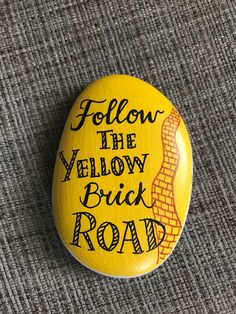 Hand painted rock- 2 sided - follow the yellow brick road on one side and theres no place like home on the other side I do custom work so please feel free to ask