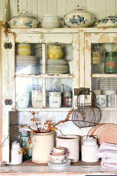 The 'rusty hinge' blog has some really beautiful photos of the chippy, primitive things that I love.  This cupboard stuffed with assorted dishware is beautiful!
