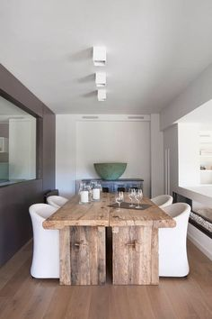 une table en bois rustique et quatre chaises blanches dans la salle à manger