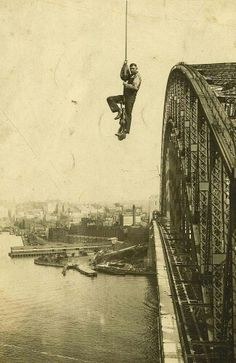 Sydney Harbour Bridge, a dogman worker riding a crane cable in 1932. Photo shared by the State Library of NSW. v@e.