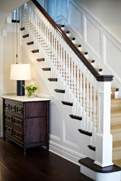 A custom birch and bamboo dresser with a marble top creates a beautiful storage space in this entryway. A sleek black lamp lights the adjacent stairwell, emphasizing the beautiful white stair railing and banister.