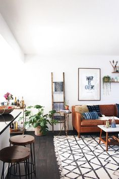 Airy and open modern living space with word art poster, brown leather couch, graphic black and white rug, and bar stools