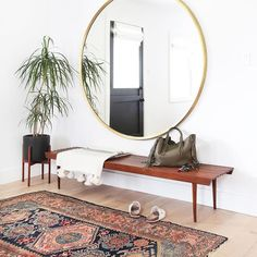 entryway with rug and circular mirror