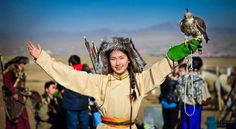 Young mongolian woman in traditional costume dressed for  hunter. with berkut on her hand
