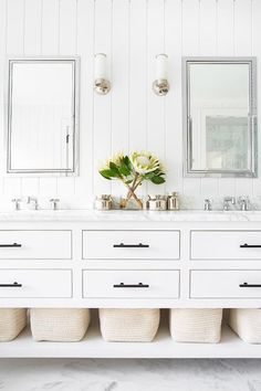 A Restoration Hardware Hutton Double Washstand sits on marble floor tiles and is contrasted with oil rubbed bronze pulls topped with a white marble countertop fitted with polished nickel knobs.