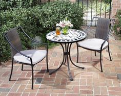 Home Style 5605-340 3-Piece Outdoor Bistro Set, Black Finish. 3-piece bistro set includes outdoor dining table and two laguna arm chairs. The bistro table features a table top constructed of natural octagon marble tiles with black square marble tile accents. Adjustable, nylon glides prevent damage to surfaces caused by movement and provide stability on uneven surfaces. Chair features a two-tone, walnut brown synthetic-weave seat and back over a powder coated steel frame in a black finish....