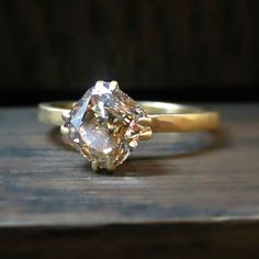 You've never seen a gold solitaire like ring 18! A fancy yellow brown Cushion Modified Brilliant cut diamond (1.56ct) is set on its corners in double prongs. Can't you just see it paired with a wide hammered gold band? Contemporary, in a hammered, satin finish 18k gold mounting. $6400, call (212) 677-9991 to purchase. Includes grading report for center stone. #doyleanddoyle #doyledoylerings #diamondsolitaire #fancybrowndiamond #cushioncutdiamond #lovegold
