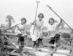 Members of the Womens Land Army climbing over a gate on a British farm during the First World War.