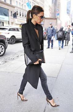Victoria Beckham looking glamorous on the streets of New York in black skinny jeans, leopard print heels and a taupe and black top.