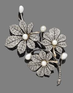A late 19th century pearl and diamond spray brooch, by Mellerio dits Meller. Of foliate design, the detachable leaves set with rose-cut diamonds and highlighted with 5.0mm-6.5mm baroque pearls, mounted in silver and gold, maker's mark MM, French assay mark, pearls untested, brooch fittings and extra screw provided, one diamond deficient, length 9.0cm