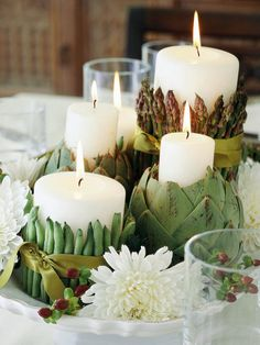 What better way to celebrate the Thanksgiving harvest feast than by creating a centerpiece using gorgeous green vegetables. To make the asparagus- and green bean-wrapped candles, stretch two sturdy rubber bands around a white pillar candle, then insert vegetable stalks underneath the band. Cover the bands with satin ribbon, and decorate the platter with a few white mums and coffee berry sprigs.