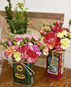 Latas de azeite servem como cachepôs. Um barbante amarrado na borda adiciona bossa ao arranjo.  Aí basta caprichar na mistura de flores e cores.