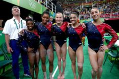 . RIO DE JANEIRO, BRAZIL - AUGUST 07: (L to R) Coach Mihai Brestyan, Simone Biles, Gabrielle Douglas, Madison Kocian, Lauren Hernandez and Alexandra Raisman of the United States pose for photographs after Women's qualification for Artistic Gymnastics on Day 2 of the Rio 2016 Olympic Games at the Rio Olympic Arena on August 7, 2016 in Rio de Janeiro, Brazil (Photo by Tom Pennington/Getty Images)