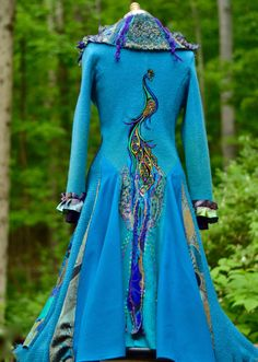 Peacock patchwork long sweater COAT with artful details is handcrafted from up cycled boiled wool sweater, wool fabrics and embellished with a peacock appliqués, felted details, peacock brooch, beaded appliques and embroidery.  Sweater coat featuring *patchwork mixed textures collar, *embroidered peacock applique, *closure: buttons, *oversized pixie pocket, * silk ruffle cuffs, * extra wide skirt.  Sustainable, eco friendly and environmentally responsible garment.  Bust: 39- 40 (99- 101,5…
