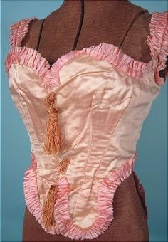 Pink silk satin corselette, circa 1860,  with tassels, trimmed with a darker pink silk satin trim, hand-stitched by a great seamstress from the mid 1800's. Four bones.  Closes in the front with tiny hooks/eyes. Offered for sale by antiquedress.com