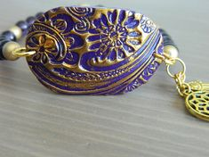 Stretch bracelet with a purple-gold polymer charm connector and two small golden charms with purple glass beads