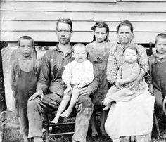 This is a portrait of a rural family with five young children.  This photograph was taken by traveling photographer Albert J. Ewing, ca. 1896-1912. Like most of Ewing's work, it was likely taken in southeastern Ohio or central West Virginia.