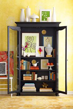 I love the idea of treating a display case like a bookshelf – offsetting stacks of books with small collectibles and art.  Source