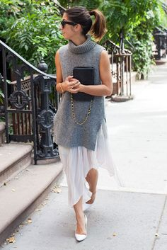 spring work outfits - 30 Spring Work Outfits To Try Right Now: Fashion Blogger 'This Time Tomorrow' wearing a grey sleeveless turtleneck knit tunic, a white chiffon midi skirt, white pointy toe pumps, black sunglasses and a black shoulder bag