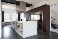 cocina con isla central de obra para fregadero y zona de cocción, módulo empotrado y suelo de baldosas color gris