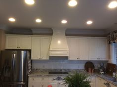 Custom hood range in kitchen with white cabinets and marble countertop