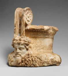 Marble fragment of a volute krater. Roman, 1st–2nd century CE. A large mask of a bearded Dionysus adorns the base of the handle, while grape leaves carved in low relief spread out behind it.