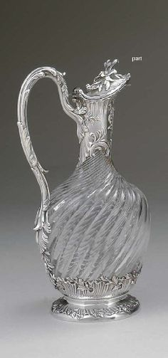 TWO FRENCH SILVER-MOUNTED GLASS CLARET JUGS   MARK OF LAPARS DE BEGUIN, PARIS, 20TH CENTURY   Each of baluster form, the first with spiral-fluted glass, on shaped square base, with silver leaf calyx, leaf-clad silver neck and pierced handle marked under base, handle, neck mount and cover, the second with spiral-fluted glass, on circular foot, with fluted silver base, leaf-clad handle, neck mount and cover, marked on neck mount  The first and larger 12¼ in. (31.1 cm.) high