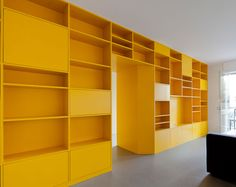 """Portuguese architects Pedro Varela and Renata Pinho have recently completed the renovation of an apartment in Portugal. For this old apartment that had to deal with very specific issues, the result is very yellow, pop style, 1970's inspired with playful shapes and geometric volumes. Of course, the main element throughout the renovated apartment is the large yellow storage piece which is totally transformable and also acts as a partition between the communal spaces."""