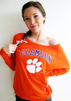 "$37.99    Comfy-chic. This lightweight, supersoft jersey slub long sleeve tee features dolman sleeves and a wide neck that can be worn off the shoulder. Easy, relaxed fit that provides subtle warmth ideal for the spring, fall or cool summer nights. Purple ""CLEMSON"" block print and white paw print application. Longer length sleeves and 2"" self-fabric banded bottom and sleeve hems. Orange.    ~ Officially licensed product  ~ 100% Cotton Jersey Slub  ~ Stadium Chic  ~ Made in the USA"