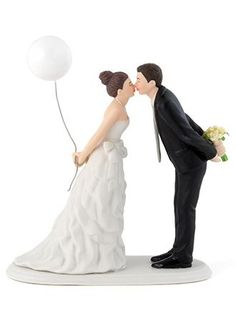 "This cake topper features a couple sweetly leaning forward for a kiss as husband and wife! Wearing a beautiful bowed dress and clasping a balloon, this beautiful bride is shown leaning towards her one true love as he holds onto her bouquet. Features and Facts:  Measurements:  5 1/8"" W x 5 1/2"" H x 2 3/8"" Diam.  Material:  Hand Painted.  Hair color as shown in picture."