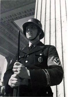 "An SS-Allgemeine guardsman part of the ""Deutschland"" division guards the entrance of the Ehrentempel, an honor hall dedicated to the original 16 National Socialists who gave their lives in service to Hitler and the Party after being fatally shot by military police during the 1923 Beer Hall Putsch in Munich."